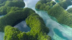 Aerial shot Palau Rock islands and marine lake on very calm morning with calm water reflecting sky as small boat passes through a channel