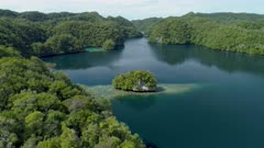 Aerial shot revealing Palau Rock islands on very calm morning with calm water reflecting sky