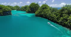 Aerial shot of boat cruising slowly between rock islands in Palau