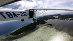 Action camera view mounted externally on tail of light aircraft flying over island in Micronesia