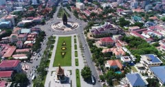 Drone footage of the Independence Monument in the city center. The camera is starting looking down at the monument and the Statue of King Father Norodom Sihanouk and is tilting up to show the Phnom Penh city center and its numerous building in construction.