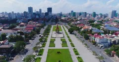 Drone footage of the Independence Monument in the city center. The camera is following the Preah Sihanouk Blvd (274) and the Preah Suramarit Blvd (268) going towards the monument. It's starting high and is slowly descending to end up in front of the Statue of King Father Norodom Sihanouk. I the background is the Phnom Penh city center and its numerous building in construction.