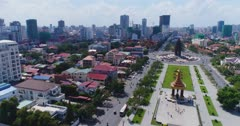 Drone footage of the Independence Monument in the city center. The camera is going towards the monument following the Preah Sihanouk Blvd (274) and the Preah Suramarit Blvd (268) and goes over the Statue of King Father Norodom Sihanouk. You can also see the Phnom Penh city center and its numerous building in construction.