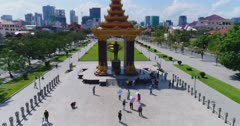 Drone footage of the Independence Monument in the city center. The camera is starting at ground level in front of the Statue of King Father Norodom Sihanouk and is ascending straight to show the Independence Monument and Phnom Penh city center with its numerous building in construction.