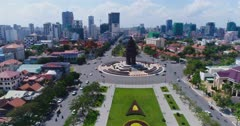 Drone footage of Phnom Penh city center. The camera is starting low facing the Independence Monument and then slowly ascending while panning left on a almost full 360 to show the Phnom Penh city center and its numerous building in construction. We can also see the mekong river, the royal palace and Phnom Penh river side.