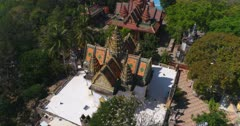Drone footage of Phnom Suntuk, Kampong Thom. The camera is turning around a temple that has white walls and a terrace with white floor surrounding it.