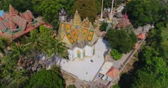 Drone footage of Phnom Suntuk, Kampong Thom. The camera is turning around a temple that has white walls and a terrace with white floor surrounding it. Wide shot so we can see the other temples around it.