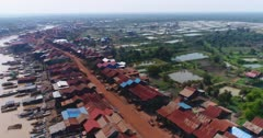 Drone footage of the stilt houses of Kampong Khleang. The camera is starting over the fields and is going sideways over the wooden houses of the village built along the Kam Flung Poo river.