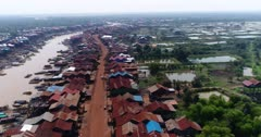 Drone footage of the stilt houses of Kampong Khleang. The camera is starting at the wooden houses of the village built along the Kam Flung Poo river and is panning right 360 degrees to show the whole village surrounded by fields.