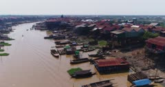 Drone footage of the stilt houses of Kampong Khleang. The camera is going over the Kam Flung Poo river showing the wooden houses of the village built along it. A lot of local boats are parked in front of the houses.