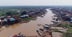Drone footage of the stilt houses of Kampong Khleang. The camera is showing the Kam Flung Poo river with the wooden houses of the village built along it and is descending.  A lot of local boats are parked in front of the houses.