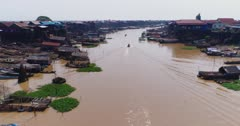 Drone footage of the stilt houses of Kampong Khleang. The camera is following the Kam Flung Poo river going over a boat that is cruising on it. A lot of local boats are parked in front of the wooden houses of the village built along the river.