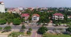 Drone footage of Battambang city. The camera is starting low over a park in the middle of the town facing East with the Sangker river behind and is ascending showing the eastern part of the city.