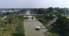 Drone footage of Battambang city. The camera is starting low over the Sangker river facing South and is going backward following the river while ascending.