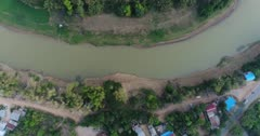 Drone footage of the south part of Battambang. The camera is facing down at a birdeye angle showing the Sangker river starting low and ascending straight.