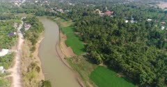 Drone footage of the south part of Battambang. The camera is starting high and is descending while going sideways over the Sangker river, showing the fruit and vegetable plantations around the river and some local houses built along the dirt roads close by.