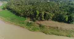 Drone footage of the south part of Battambang. The camera is going over the Sangker river sideways slowly descending, showing the bank of the river with the plantations along it and some local houses built along the dirt roads close by. It is starting high and is descending while going sideways over the river.