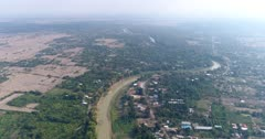 Drone footage of the south part of Battambang. The camera is starting very high and is descending facing South, showing the Sangker river stretching far away, the fruit and vegetable plantations around it and some local houses built along the dirt roads close by.