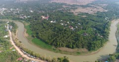 Drone footage of the south part of Battambang. The camera is starting high and is descending following the Sangker river sideways, showing the plantations along the river and some local houses built along the dirt roads close by. It is starting high and is descending while going sideways over the river.