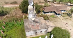 Drone footage of the north part of Battambang. The camera is facing down at a massive buddha statue 20m tall in the Ek Phnom Temple area and is turning around it slowly descending and tilting up at the same time showing the temple in the background. Some pigeons are flying by.
