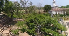 Drone footage of the north part of Battambang. The camera is ascending straight in front of a tree, showing the statue and the rice fields in the background.