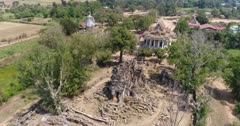 Drone footage of the north part of Battambang. The camera is going over the Ek Phnom area starting at the old temple and going towards the Pagoda and the Buddha statue .