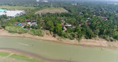 Drone footage of the northern part of Battambang, Cambodia. The camera is starting following a local boat cruising on the Sangker river and outrun it showing the fields and houses built along the water.