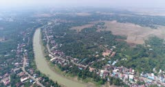 Drone footage of the northern part of Battambang, Cambodia. The camera is following the Sangker river showing the fields and houses built along it. It is starting very high and slowly descending.