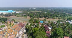 Drone footage of the northern part of Battambang, Cambodia. The camera is starting at the Wat Keo with its beautiful pagoda and then is going over the Sangker river showing the fields and houses built along it.