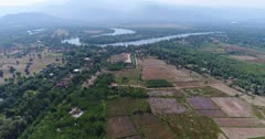 Drone footage of the northern part of Kampot, Cambodia. The camera is going over fields and swamp cover with nipa palm trees heading towards the Praek Tuek Chhu river.