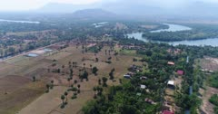 Drone footage of the northern part of Kampot, Cambodia. The camera is going over dried rice fields scattered with sugar palm trees (Borassus flabellifer) heading towards the Praek Tuek Chhu river.