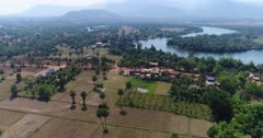 Drone footage of the northern part of Kampot, Cambodia. The camera is going over dried rice fields scattered with sugar palm trees (Borassus flabellifer) following the Praek Tuek Chhu river.