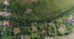 Drone footage of the northern part of Kampot, Cambodia. The camera is facing down at a birdeye angle and is going over houses built near the Praek Tuek Chhu river, a swamp cover with nipa palm trees and dried rice fields.
