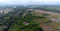 Drone footage of the northern part of Kampot, Cambodia. The camera is starting over a swamp cover with nipa palm trees and going sideways showing dried rice fields scattered with sugar palm trees (Borassus flabellifer) along the Praek Tuek Chhu river.