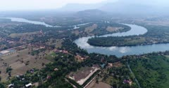 Drone footage of the northern part of Kampot, Cambodia. The camera is going sideways along the Praek Tuek Chhu river showing dried rice fields scattered with sugar palm trees (Borassus flabellifer).