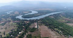 Drone footage of the northern part of Kampot, Cambodia. The camera is going over fields and swamp cover with nipa palm trees slowly descending and heading away from the Praek Tuek Chhu river.
