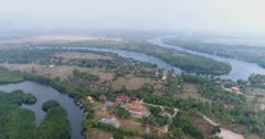 Drone footage of the northern part of Kampot, Cambodia. The camera is showing the Praek Tuek Chhu river with its lush tropical vegetation including nipa palm trees and the local houses built around it.
