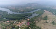 Drone footage of the northern part of Kampot, Cambodia. The camera is slowly descending showing the Praek Tuek Chhu river with its lush tropical vegetation including nipa palm trees growing along it, the Toek Vil Pagoda and dried rice fields scattered with sugar palm trees (Borassus flabellifer).