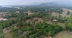 Drone footage of the northern part of Kampot, Cambodia. The camera is slowly descending showing the Praek Tuek Chhu river with its lush tropical vegetation, the Toek Vil Pagoda and dried rice fields scattered with sugar palm trees (Borassus flabellifer).