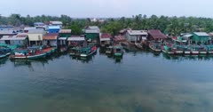 Drone footage of the southern part of Kampot, Cambodia. The camera is starting over the water of the Prek Kampong river facing colorful fishing boat parked in front of houses built on the bank of the river and is going away while ascending showing lds in the background.