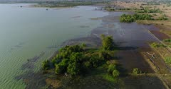 Drone footage of Brateak Krola Lake between Kampot and Kep, Cambodia. The camera is going along the shore of the lake while slowly panning right to end up over its green water.