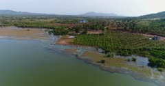 Drone footage of Brateak Krola Lake between Kampot and Kep, Cambodia. The camera is going over the green water of the lake following its shore where fields and scattered trees are mixing.