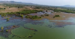 Drone footage of Brateak Krola Lake between Kampot and Kep, Cambodia. The camera is facing the shore of the lake and is going away from it while slowly panning left to end up over its green water.