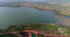 Drone footage of Brateak Krola Lake between Kampot and Kep, Cambodia. The camera is facing down at the lake with its green wwater and is going sideways following its shore where fields and scattered trees are mixing