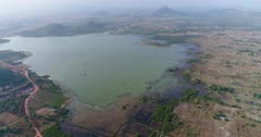 Drone footage of Brateak Krola Lake between Kampot and Kep, Cambodia. The camera is facing the lake showing it entirely and is descending while going towards its shore where fields and scattered trees are mixing.