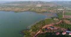 Drone footage of Brateak Krola Lake between Kampot and Kep, Cambodia. The camera is showing the southern part of the lake with its green water and fields along its shore and is descending while going towards the fields.