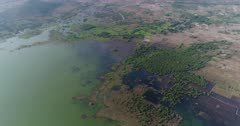 Drone footage of Brateak Krola Lake between Kampot and Kep, Cambodia. The camera is going over the green water of the lake following its shore where fields and scattered trees are mixing and is slowly tilting up.