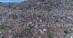 Drone footage of the main official rubbish dump in Bali. A 30 hectares pile of waste (including plastic, organic, glass, furniture and more) that goes up to 20m high. The camera is going sideways along the few meters high stairs like piles of trash and is going up showing the road that goes between the rubbish mountains.