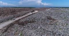 Drone footage of the main official rubbish dump in Bali. A 30 hectares pile of waste (including plastic, organic, glass, furniture and more) that goes up to 20m high. The camera is going along a 3 meters high stair like pile of trash to finish showing the waste treatment facility.
