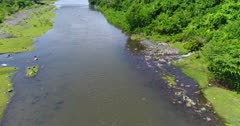 Drone footage of a small river that is flowing into the Tukad Yeh Unda river bringing all the trash with it. Panning shot starting at the plastic waste at the bank of the river and turning to a few cows eating grass on the other side.